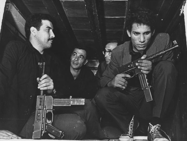 Saadi Yacef, as revolutionary leader El-hadi Jaffar (second from left) and Brahim Haggiag (right) as revolutionary leader Ali La Pointe in a scene from Gillo Pontecorvo's THE BATTLE OF ALGIERS (1965). Photo courtesy Rialto Pictures.